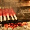 tizigoiner carne arrotolata sul bastone che cuoce sulla brace del camino